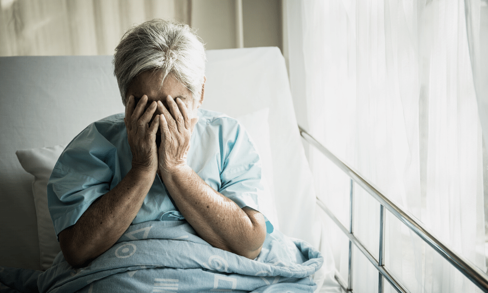 an elderly woman in bed crying