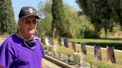 Leonard Tavernetti stands in front of grave markers in Redlands
