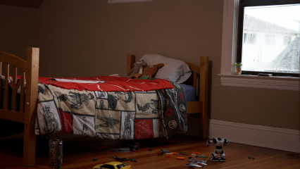 A photo of an empty child's bed with toys laying on the floor.