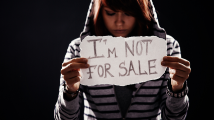Female human trafficking victim holds sign reading I'm not for sale.